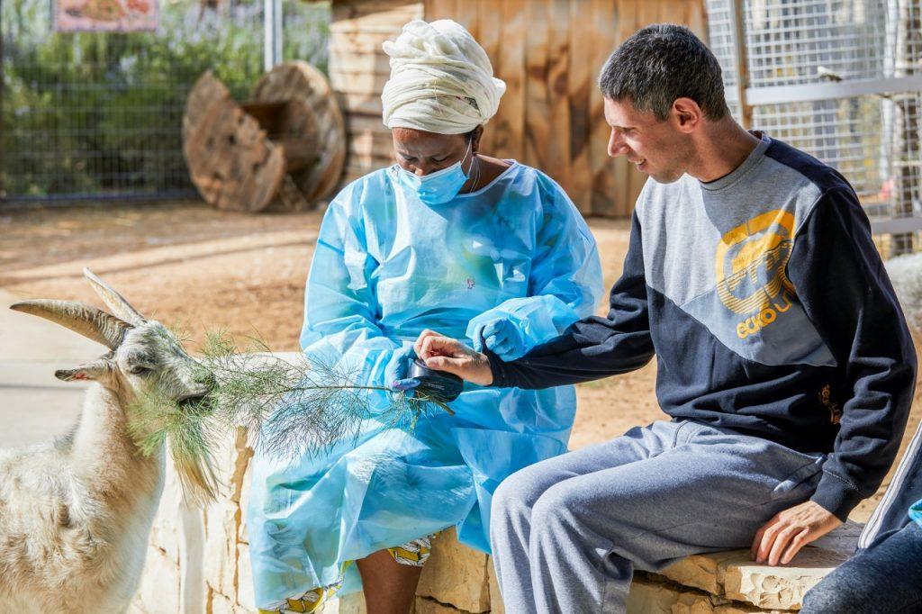 דייר ומטפלת מאכילים עז Resident and caregiver feeding a goat