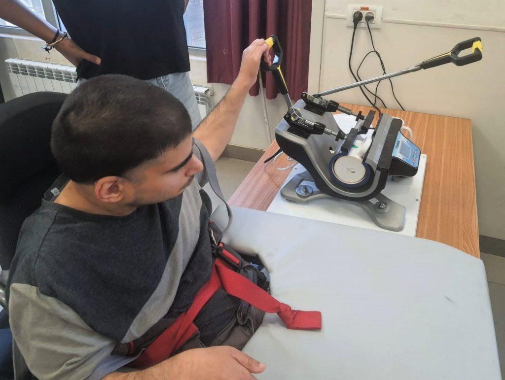 חניך מפעיל מכונה במפעל שיקום Resident working a machine in the rehab workshop