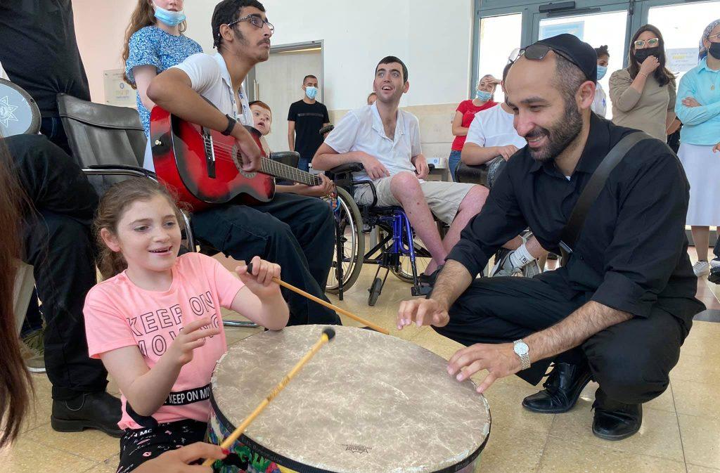 Philharmonic drummer and resident playing drums נגן התזמורת מתופף עם ילדה